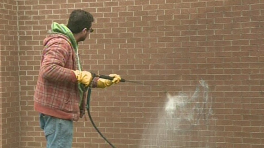 Worker tries to remove racial slurs and tags painted on Our Lady of Fatima School in Hespeler