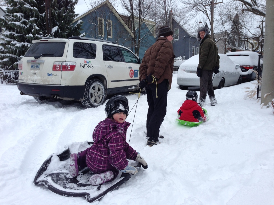 A woman pulls two kids in sleds following a snowstorm in Toronto, Thursday, Dec. 27, 2012. (Colin D'Mello / CTV Toronto)