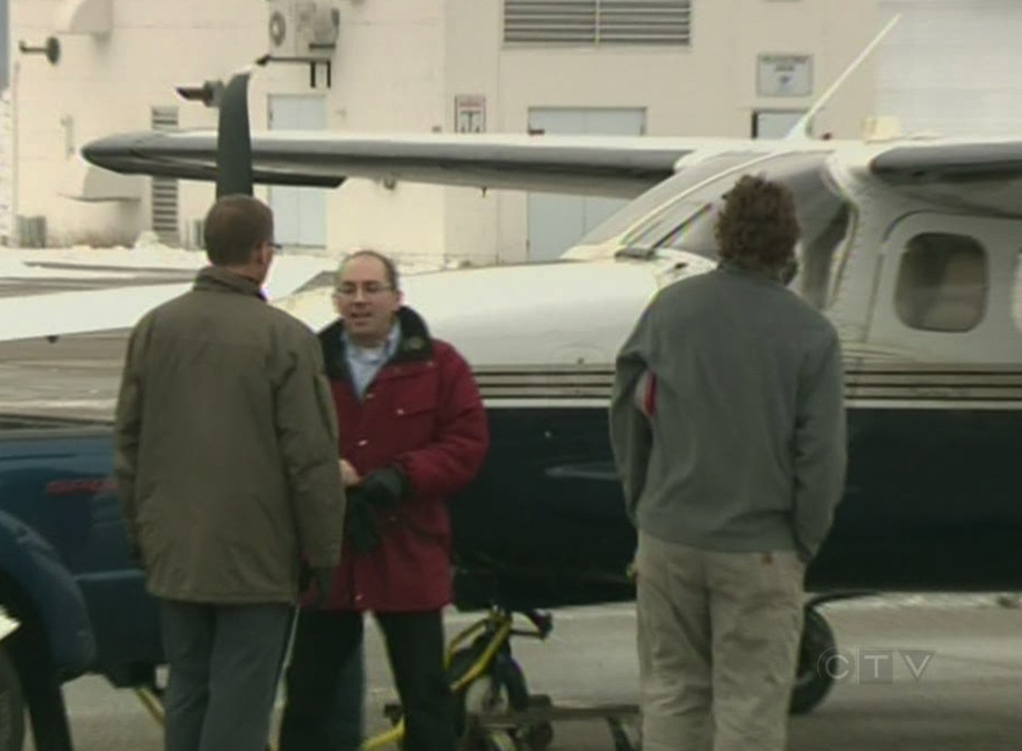 Pilot Pascal Gosselin (in red) and onlookers survey the damage after Gosselin's single-engine plane was forced out of the sky without working landing gear and landed at the Region of Waterloo International Airport on Monday, Jan. 7, 2013 (CTV Kitchener).