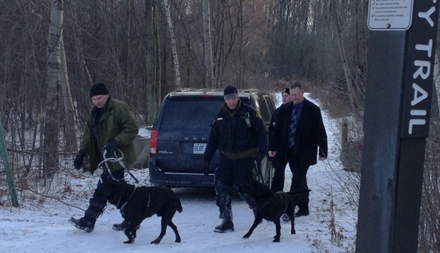 Police officers and a canine unit are seen leaving a wooded area along River Road in Kitchener, Ont., on Thursday, Jan. 31, 2013. (Nicole Lampa / CTV Kitchener)