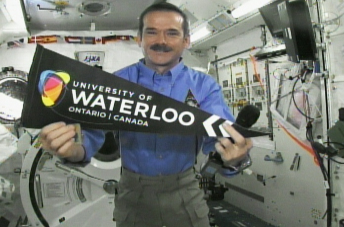 Canadian astronaut Chris Hadfield holds up a University of Waterloo pennant while speaking to the school's students from the International Space Station on Friday, Feb. 15, 2013. (CTV Kitchener)