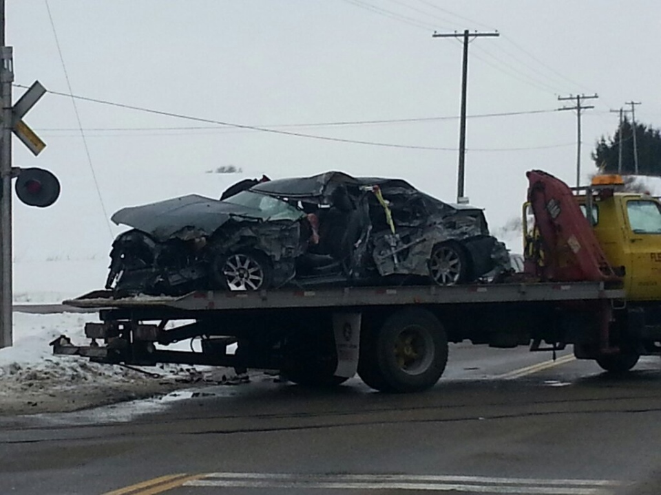 A car is towed from the scene of a collision that involved a train near Woodstock. Feb. 24 2013