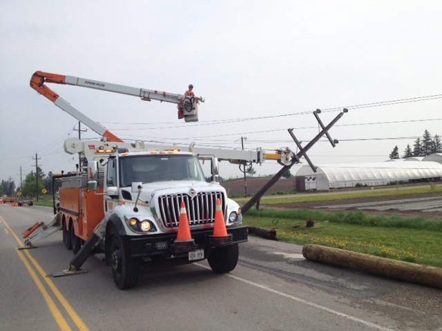 Power crews work to repair downed hydro poles on Katherine Street near Winterbourne, Ont., on Tuesday, May 21, 2013. (Kevin Doerr / CTV Kitchener)
