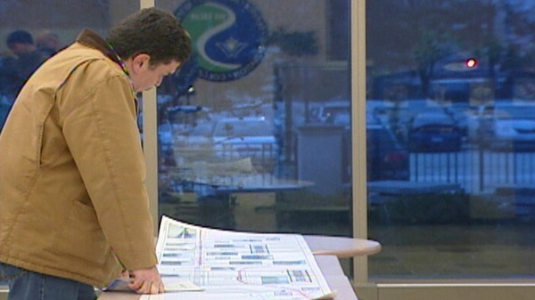 A resident looks at Waterloo Region's rapid transit plans at a public consultation in Kitchener, Ont. in Feb. 2011.