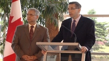 Conservative MP Gary Goodyear, left, and Ontario Minister for Training and Universities John Milloy, right, speak in Cambridge, Ont. on Tuesday, July 5, 2011.