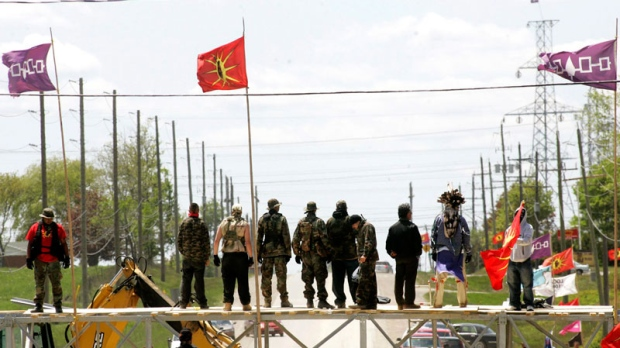 Six Nations protesters stand on top of their barricade moments before taking it down in Caledonia, Ont., near Hamilton on May 23, 2006. (Nathan Denette/THE CANADIAN PRESS)