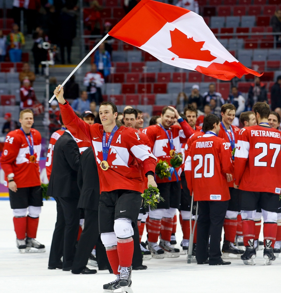 Team Canada forward Jonathan Toews waves the Canadian flag after Canada beat Sweden 3-0 in the men's gold medal ice hockey game at the 2014 Winter Olympics in Sochi, Russia, Sunday, Feb. 23, 2014. (AP / Matt Slocum)