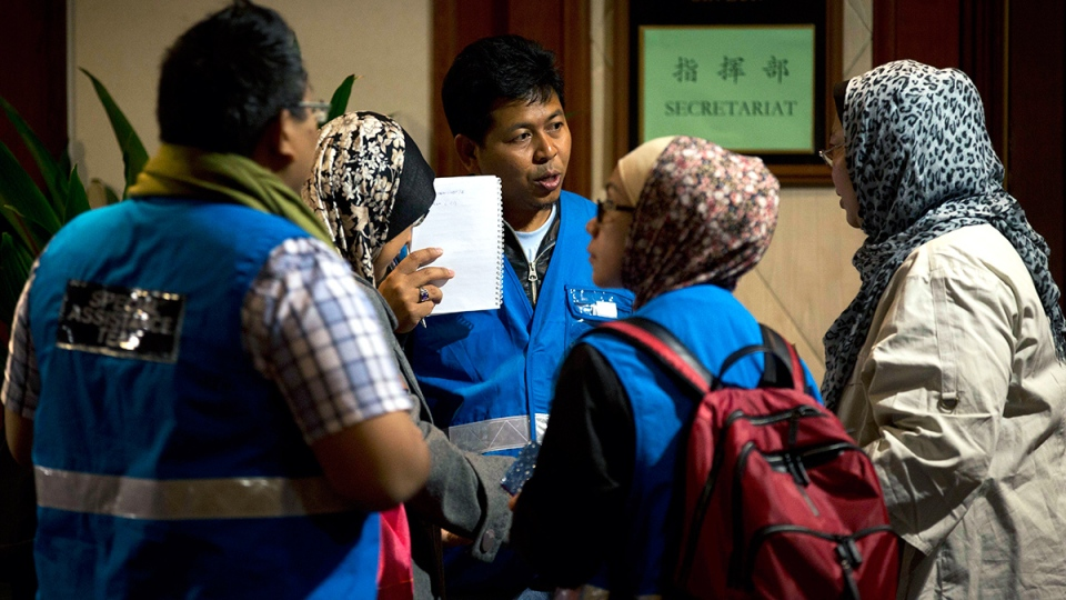 Members of a special assistance team from Malaysia chat at a hotel prepared for relatives or friends of passengers aboard a missing Malaysian Airlines jetliner, in Beijing, China, Sunday, March 9, 2014. (AP / Andy Wong)
