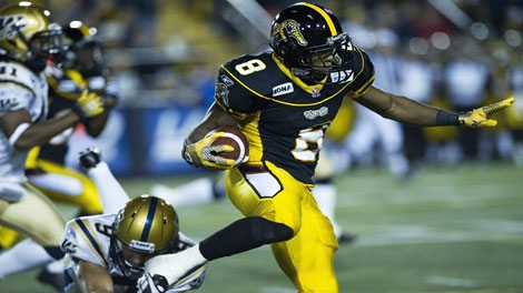 Hamilton Tiger-Cats running back Marcus Thigpen, right, leaps over Winnipeg Blue Bombers punter Mike Renaud, left, during first half CFL football action in Hamilton, Ont., on Friday, Oct. 7, 2011. THE CANADIAN PRESS/Nathan Denette
