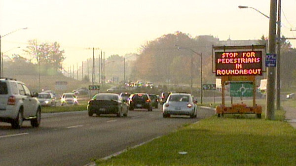 A sign asks motorists to stop for pedestrians at the Homer Watson Boulevard and Block Line Road roundabout.