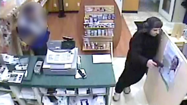 A man wanted in connection with a pharmacy robbery is seen in this image taken from security video in Kitchener, Ont. on Friday, Dec. 9, 2011. (Courtesy Waterloo Regional Police Service)