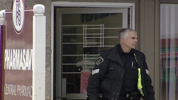 A Waterloo Regional Police Service officer is seen outside the Central Pharmasave in Kitchener, Ont. on Monday, Jan. 9, 2012.
