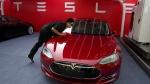 A worker cleans a Tesla Model S sedan in Beijing on April 22, 2014. (AP / Ng Han Guan)