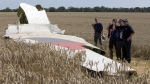 In this Aug. 1, 2014 file photo, investigators examining a piece of the Malaysia Airlines Flight 17 plane crash near the village of Hrabove, Donetsk region, eastern Ukraine. (AP /  Dmitry Lovetsky)