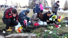 Family and friends place flowers at the scene of the fatal van crash in Hampstead, Ont., on Tuesday, Feb. 7, 2012. (Denise Kimmel / CTV News)