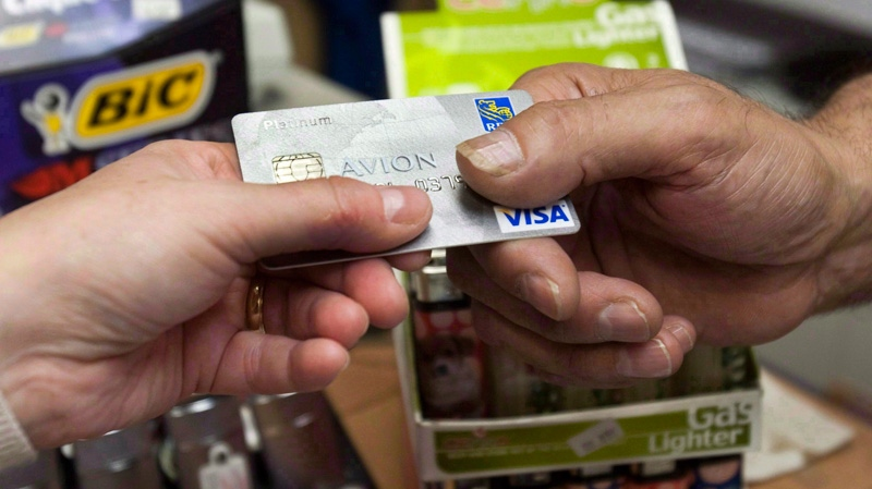 A consumer pays with a credit card at a store in Montreal on July 6, 2010. (Ryan Remiorz / THE CANADIAN PRESS)