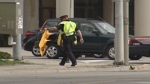 A police officer clears debris after high winds in Waterloo Region, Ont. on Monday, April 16, 2012.