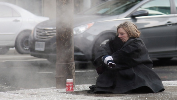 A woman tries to keep warm on a grate on a street corner in downtown Toronto on Monday, Jan. 5, 2014. (Colin Perkel / THE CANADIAN PRESS)