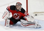 A puck shot by Pittsburgh Penguins defenseman Simon Despres, enters the net of New Jersey Devils goalie Cory Schneider as the Penguins beat the the Devils 2-1 during overtime of an NHL hockey game, Friday, Jan. 30, 2015, in Newark, N.J. (AP Photo/Julio Cortez)