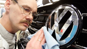A worker polishes a Volkswagen emblem on Feb. 28, 2006. (Kai-Uwe Knoth / AP)