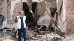 In this Friday, Oct. 16, 2015 photo, Christopher Stokes, the general director of the medical charity, Doctors Without Borders, which is also known by its French abbreviation MSF, stands amid the charred remains of the organization's hospital, after it was hit by a U.S. airstrike in Kunduz, Afghanistan. (Najim Rahim via AP)