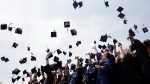 Newly minted local college graduates take part in the annual Toss Your Caps class photo Friday, May 8, 2015, on the steps of the Philadelphia Museum of Art in Philadelphia. (AP / Matt Rourke)