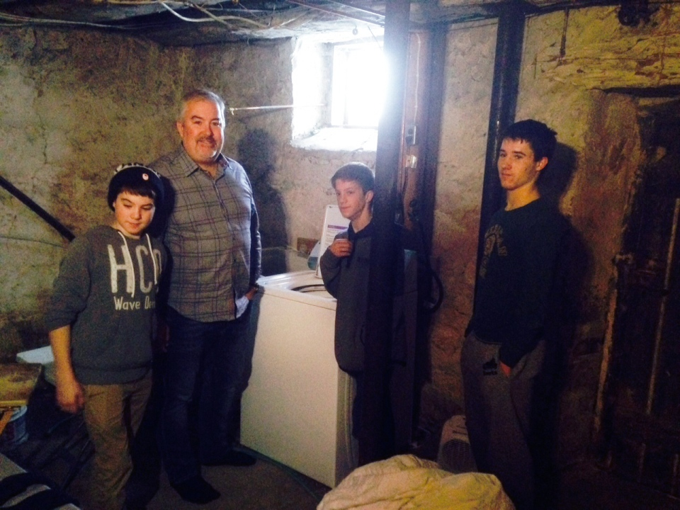 John Schultz and his teenage sons stand around a washing machine in their home on Thursday, Jan. 21, 2016. Schultz has posted a tongue-in-cheek ad on Kijiji looking for a 'part-time wife'. (Abigail Bimman / CTV Kitchener)