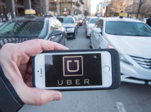 The Uber logo is seen in front of protesting taxi drivers who were depositing a request for an injunction against the ride sharing company at the courthouse in Montreal on Tuesday, February 2016. (Ryan Remiorz / THE CANADIAN PRESS)