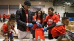 Toronto Raptors Demar DeRozan, second from left, is joined by his wife Kiara, centre, two year old daughter Diar, left, and fellow Raptor Kyle Lowry, second from right, and his four year old son Karter as they sort food donations for The Daily Bread Food Bank in Toronto on Friday, February 12, 2016. (Chris Young / THE CANADIAN PRESS)