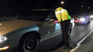 A Toronto police officer questions a driver at a roadside stop.