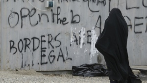 A woman walks past graffiti written on a container at the northern Greek border point of Idomeni, Greece on Wednesday, May 4, 2016. (AP / Gregorio Borgia)