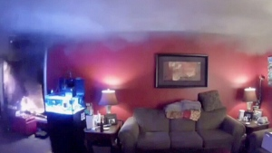 Fire engulfs a Fort McMurray couple's home as they watch from a smartphone.