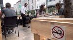 A no-smoking sign is seen on a patio Wednesday, May 25, 2016 in Montreal. Quebec's anti-smoking law will kick in Thursday prohibiting smoking on outdoor patios. (Paul Chiasson / The Canadian Press)