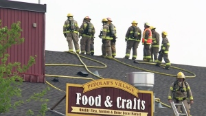 Firefighters battle a fire at the St. Jacobs Farmers' Market from the roof of Peddlar's Village on Thursday, May 26, 2016.