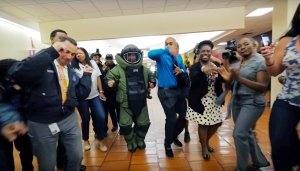 In this undated frame from video provided by the Miami Police Department, officers, including a member of the Bomb Squad in protective gear, and staff dance at Miami police headquarters. In a now-viral sensation, police officers across the U.S. are dancing an updated version of the running man to a catchy 1990s hip hop song, 'My Boo' by Ghost Town DJ's, in videos that have included professional sports mascots, cheerleading squads and at least one explosion. (Miami Police Department via AP)