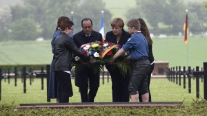 French President Francois Hollande, left, and German Chancellor Angela Merkel lay a wreath at a German cemetery in Consenvoye, northeastern France, Sunday May 29, 2016, during a remembrance ceremony to mark the centenary of the battle of Verdun. (Jean Christophe Verhaegen/Pool Photo via AP)