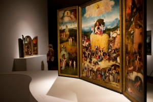 In this Friday, May 27, 2016 photo, a man stands next to 'The Haywain' triptych painting, right, by Dutch artist Hieronymus Bosch during an exhibition at the Prado museum in Madrid, Spain. The exhibition for the 500th anniversary of Bosch that is billed as a once-in-a-lifetime review of the best and most of the Renaissance master was inaugurated by Spain's King Felipe VI Monday May 30, 2016. (AP Photo/Francisco Seco)