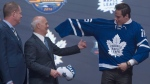 Toronto Maple Leafs general manager Lou Lamoriello helps first overall pick Auston Matthews as he puts on his sweater at the NHL draft in Buffalo, N.Y. on Friday June 24, 2016. (Nathan Denette / THE CANADIAN PRESS)