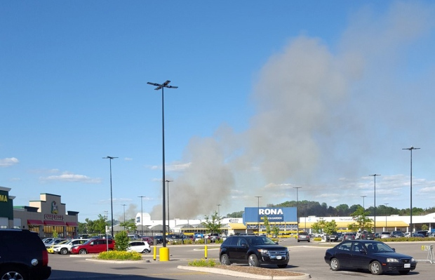 Smoke billows from a grass fire alongside Highway 401 in Cambridge on Wednesday, June 29, 2016. (@IMC_Kevin / Twitter)