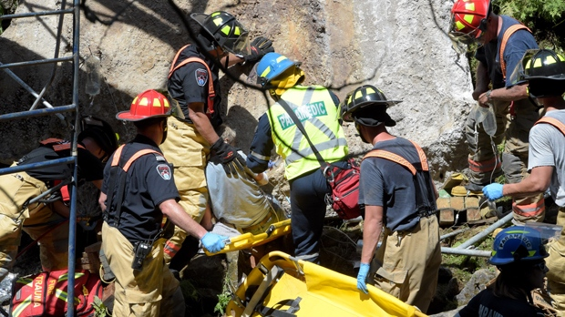 Firefighters and paramedics assist a man who was trapped by a concrete beam in the Hamilton area on July 21. (Andrew Collins)