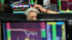 A woman scratches her head as she monitors stock prices at a brokerage house in Jiujiang city in central China's Jiangxi province on Wednesday July 27, 2016. (Chinatopix)