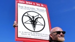 Chris Bridges holds a sign for The Satanic Temple during a protest outside of an all-day prayer rally headlined by Louisiana Gov. Bobby Jindal in Baton Rouge on Jan. 24, 2015. (AP / Jonathan Bachman)