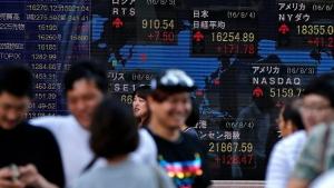 People walk past the electronic board showing the Nikkei stock index, left, in Tokyo, Thursday, June 16, 2016. (AP / Shuji Kajiyama)
