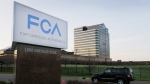 A vehicle moves past a sign outside Fiat Chrysler Automobiles world headquarters in Auburn Hills, Mich. on May 6, 2014. (AP Photo/Carlos Osorio, File)