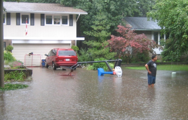 A man stands in knee-deep waters in the Forest Hill neighbourhood of Kitchener on Thursday, Aug. 25, 2016. (Ken Beckner)