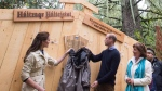The Duke and Duchess of Cambridge remove a rain jacket to unveil a plaque in the Great Bear rainforest in Bella Bella, B.C., Monday, Sept 26, 2016. THE CANADIAN PRESS/Jonathan Hayward