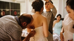 Ibrahim Halil Dudu, a tailor who had only arrived in Canada a few days earlier as a refugee, fixes Jo Du's wedding dress. (Lindsay Coulter Photography)