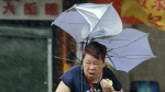 A woman eats and struggles with her umbrella against powerful gusts of wind generated by typhoon Megi across the island in Taipei, Taiwan on Tuesday, Sept. 27, 2016. (AP / Chiang Ying-ying)