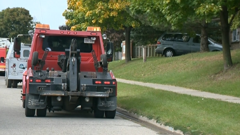 A tow truck waits to take away a van that drove into a townhome in Cambridge, Ontario. (CTV Kitchener)