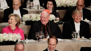 Cardinal Timothy Dolan, centre, Democratic presidential candidate Hillary Clinton, left, Republican presidential candidate Donald Trump, right, smile during the invocation at the 71st Annual Alfred E. Smith Memorial Foundation Dinner Thursday, Oct. 20, 2016, in New York. (AP / Frank Franklin II)